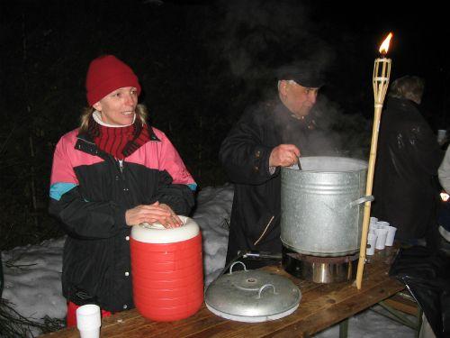 Delitev toplih napitkov ov večernem teku na smučeh ob baklah
